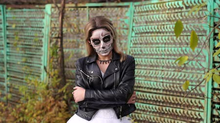 жестокий : A young girl with a creepy make-up in the form of a skull on her face in a wedding dress and a leather jacket on the background of an old rusty fence. Halloween. The image of the dead bride.