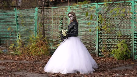 маска : A girl in a wedding dress with a terrible make-up on her face stands in the autumn against the background of an old abandoned fence. The celebration of Halloween. Halloween or horror concept.
