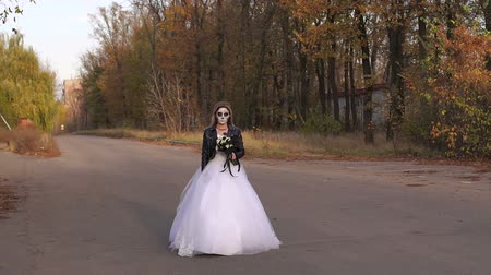 маска : A young girl with a creepy make-up in the form of a skull on her face in a wedding dress and a leather jacket going on an empty road. Halloween. The image of the dead bride. Стоковые видеозаписи