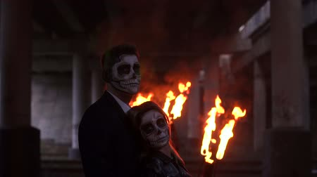 fire suit : Couple with dark skull makeup on the background of burning fire and smoke. Halloween face art. Halloween concept. Zombie. Silhouette. Slow motion.
