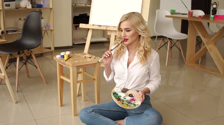 vele : A luxurious blonde with red lips poses in the drawing Studio, she is dressed in jeans and a white shirt. A young girl with a palette and brushes sitting on the floor in an art Studio. Filmati Stock