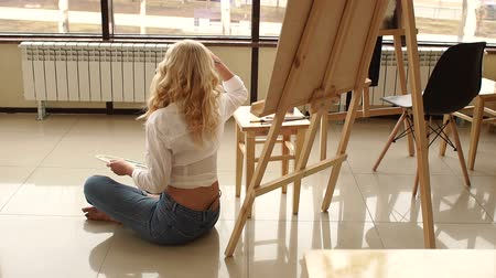 разорвал : A young sexy girl in jeans and a white shirt sits on the floor leaning against a wooden easel, she holds a palette with tassels and looks out the big window. Стоковые видеозаписи