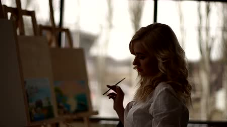 szál : Silhouette of the artist with a brush in her hand, she stands near the canvas and thinks what to draw.
