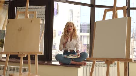 sill : A beautiful girl with blond hair sits on the windowsill of a large window with a palette and brushes in her hand. Portrait of a dreamy artist in the Studio for drawing. Art. Stock Footage