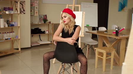 malarstwo : A sexy girl in a black dress sits on a chair near a wooden easel in the Studio for drawing, she has a red hat on her head. Blonde with curly hair posing in the art Studio. Slow motion. Wideo