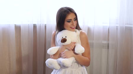 juffrouw : A young girl with long hair in a white dress sits on the floor near the window and hugs a white Teddy bear. Slow motion.