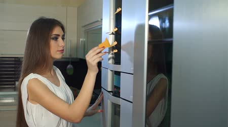 magnets : Close-up girl takes a note from the refrigerator door. Slow motion. Woman writing message on note stuck to refrigerator door at home. Woman holding empty note near refrigerator door in kitchen. Stock Footage