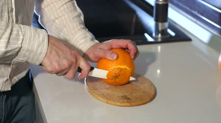 smaak : Male cutting orange with knife. Healthy lifestyle concept. Male hands cutting fresh orange on kitchen. Man cutting orange with knife. Slow motion. Close-up. Stockvideo