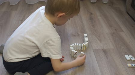 ロジック : Close-up of a little boy playing dominoes sitting on the wooden floor of the house, he builds a Domino bones track. Domino principle. The fall of the dominoes. Slow motion.