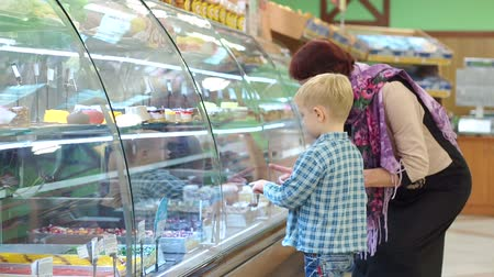supermarket food : An old grandmother with a small grandson in the supermarket choose sweets on the counter. Portrait of an elderly woman with a child in the supermarket. A grandmother with a grandson to buy a cake.