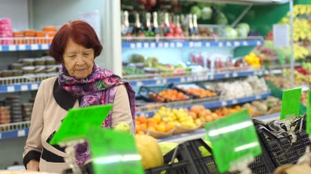 ochenta : An elderly woman with wrinkles on her face chooses and buys products in the supermarket. Slow motion. Cute grandmother buys vegetables in the grocery store.