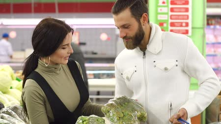 vegetarianismo : Beautiful young smiling couple choosing cauliflower in supermarket together. Beautiful young couple choosing products in supermarket and looking at each other with smile. Vegetarianism. Vídeos