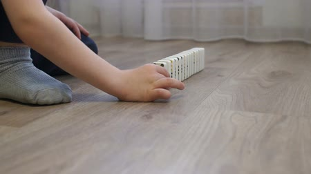pult : Close-up of a little boy playing dominoes sitting on the wooden floor of the house, he builds a Domino bones track. Domino principle. The fall of the dominoes. Slow motion.