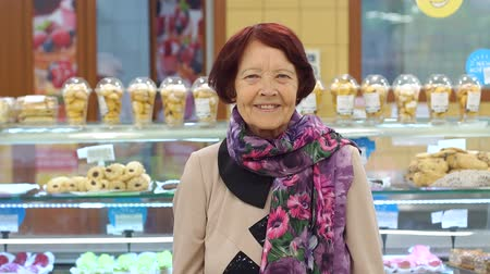 バゲット : Portrait of a cute retired woman in a grocery store in the bread Department. Grandma buys fresh bread at the supermarket.