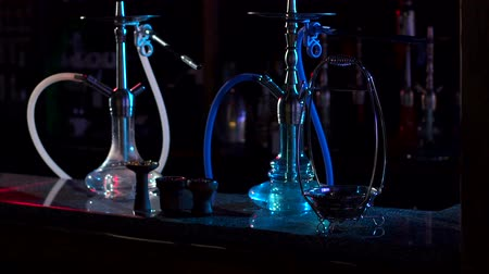 mouthpiece : Two hookahs stand on the bar counter in a hookah bar in the dark, slow motion. Hookah on a light background. Hookah stands on the bar in the hookah bar.