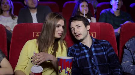 discutir : Close-up of a young couple in love sitting in a movie theater watching a movie, they discuss something while watching. Portrait of cheerful friends in the cinema chairs. Vídeos