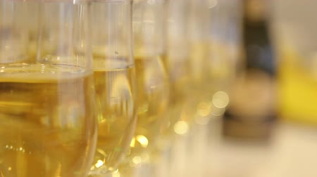 тост : Close-up of glasses of champagne in a row on a table. A lot of wine glasses with a cool delicious champagne or white wine at the bar. Alcohol background.