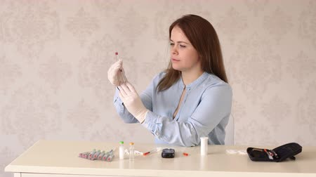 dose : A young woman with type 1 diabetes gives herself an insulin injection at home, she takes insulin with an insulin syringe.Portrait of a diabetic woman at home with a glucometer and insulin syringe pens Stock Footage
