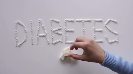 palavras cruzadas : The word DIABETES with lancets for glucometer on the table on a white background. Lay next to the sugar cubes. A womans hand takes a sugar cube. The concept of type 1 and type 2 diabetes.