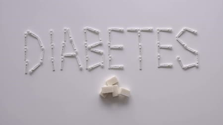 palavras cruzadas : The word DIABETES with lancets for glucometer on the table on a white background. Lay next to the sugar cubes. The concept of type 1 and type 2 diabetes. Diabetes concept.