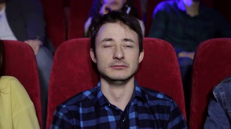 初演 : A young emotional guy watches a sad movie in a movie theater and cries, portrait. 動画素材