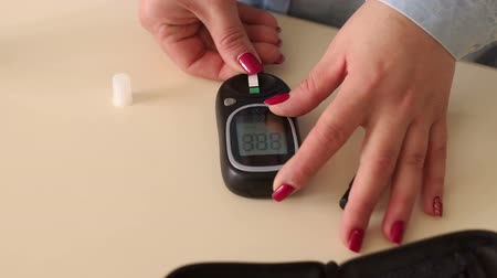 glicose : Device for measuring blood sugar level close-up. Diabetes patient measuring glucose level blood test using glucometer. Girl inserts into the glucometer test strips to measure blood at home. Vídeos
