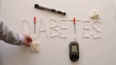 glicose : The word DIABETES is from lancets, insulin syringes, glucometer and insulin syringe pens on a white background, the childs hand puts a sugar cube next to the word. Slow motion. Theme of diabetes.