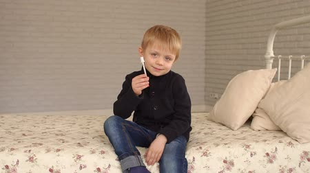 dose : A little boy sitting on the bed at home and holding an insulin syringe. Slow motion.