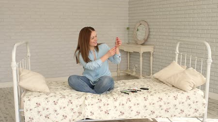 glukometr : A young diabetic woman sits on a bed at home and dials insulin in a short-acting insulin syringe, she measures her blood glucose with a glucometer and injects insulin.
