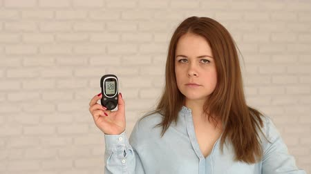 glicose : A young diabetic girl is holding a blood glucose meter with a high blood sugar level. Theme of diabetes. High blood glucose levels. Diabetes type 1. Slow motion. Portrait. Hyperglycemia.