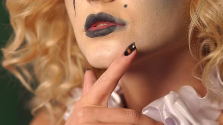 aristocrático : Close-up portrait of an excited blonde woman with make-up in halloween. Eerie makeup on the face of a girl with black streaks and black lips. Fashionable makeup for Halloween party, horror and mystery Vídeos