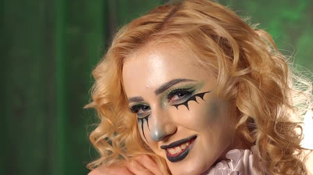 vampiro : Girl with Halloween face art on green background. Halloween and creative make-up theme. Portrait of young beautiful girl with make-up skeleton on her face.