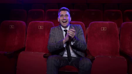 fotel : A successful businessman in a suit sits alone in a movie theater and watches a funny movie, he claps his hands. Portrait of a young successful man in an empty cinema. Wideo