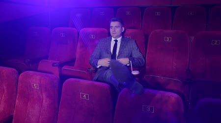 актер : A successful businessman sitting in an empty theater and watching a movie alone, he threw his legs on the chair in front.