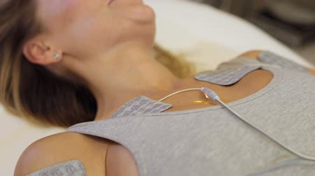elektro : A young woman lies in a cosmetic clinic on the couch and receives a biostimulating anti-cellulite body massage. Skin Care concept. Woman getting getting electro stimulation therapy to her body.