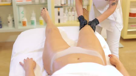 mimos : The beautician pours special massage oil onto the girl feet before the massage. The procedure of professional massage in the spa salon.