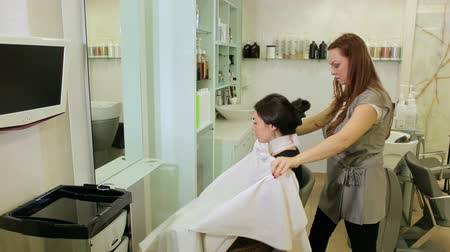 uzun saçlı : Female hairdresser is fixing collar on the neck of a young girl in a modern hair salon. Stylist puts on hairdressing collar on girl neck before cutting.