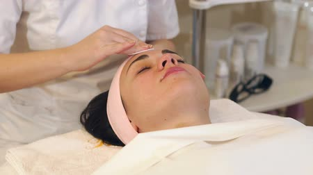 mezoterapia : Close-up beautician in black gloves wipe face with a cotton swab micellar water. Girl on facial rejuvenation procedures in the Spa. Wideo