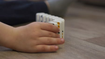 dominostenen : Close-up of a little boy playing dominoes sitting on the wooden floor of the house, he builds a Domino bones track. Domino principle. The fall of the dominoes. Slow motion.