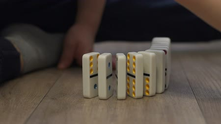 logic : Close-up of a little boy playing with dominoes on the floor of the house, he puts them next to them to alternately fall. The reaction of falling dominoes.