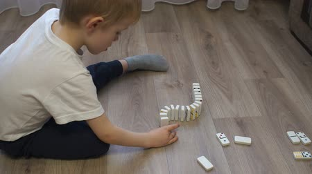 dobbelstenen : Close-up of a little boy building a long road of dominoes with multi-colored dots sitting on the floor of the house. Domino principle. Slow motion. Educational logic games.