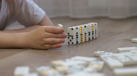 dobbelsteen : Close-up of a little boy playing with dominoes on the floor of the house, he puts them next to them to alternately fall. The reaction of falling dominoes.