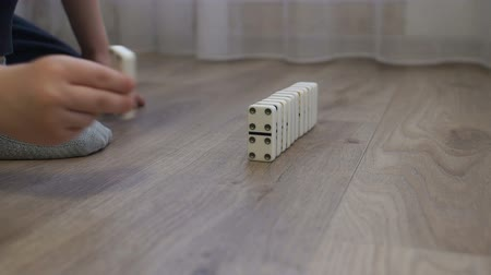 morrer : Close-up of a little boy playing with dominoes on the floor of the house, he puts them next to them to alternately fall. The reaction of falling dominoes.