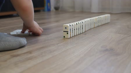 ロジック : Close-up of a little boy playing with dominoes on the floor of the house, he puts them next to them to alternately fall. The reaction of falling dominoes.