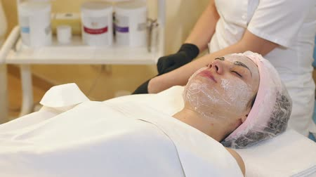 анти : Natural sheet mask for the face skin care. The cosmetologist doing procedure of cleansing and moisturizing the skin, applying a sheet mask to the face of a young woman in beauty salon. Rejuvenation. Стоковые видеозаписи