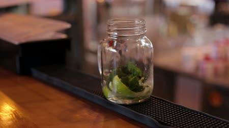 juice jar : The bartender pours sweet liquor into a glass of lime and mint, making a Mojito cocktail at the bar. Close-up of expert bartender making Mojito cocktails with lime, mint and rum in bar. Sweet syrup. Stock Footage