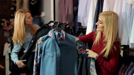 denemek : Two fashionable blonde girls choose clothes in a large clothing store. Slender young women buy fashionable clothes in a modern shopping center.