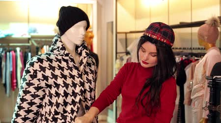 manekin : Happy girl looking at clothes on a mannequin in a clothing store, she choose an autumn black and white coat. Sale, shopping, fashion and people concept.