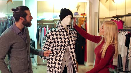 manekin : Fashionable couple in love choose their clothes in the store, they look at the clothes on the mannequin. The couple is shopping at a clothing store, they look at the coat on the mannequin.