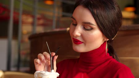elegant dessert : Close-up portrait of smiling girl with bright makeup in cafe, she is talking to friends and holding an ice cream cocktail in her hand. Stock Footage